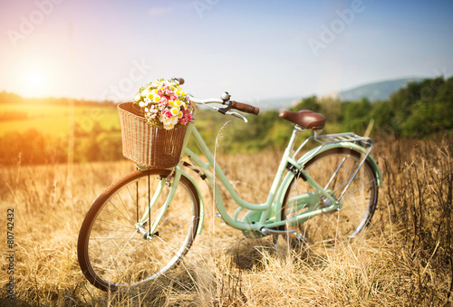 Poster Ontspanning Vintage bicycle with basket full of flowers standing in field