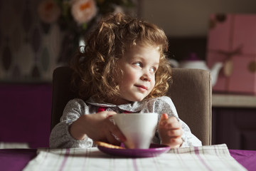 Little curly-haired girl with a cup
