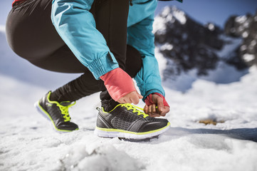 Unrecognizable woman jogging outside in sunny winter mountains