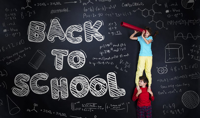Cute girl and boy learning playfully in frot of a big blackboard
