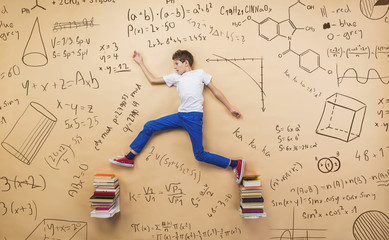 Cute boy learning playfully in frot of a big blackboard