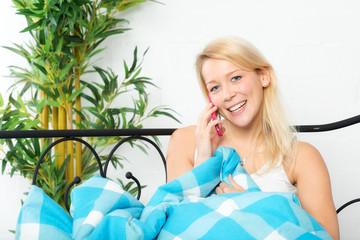Junge Frau liegt im Bett und telefoniert