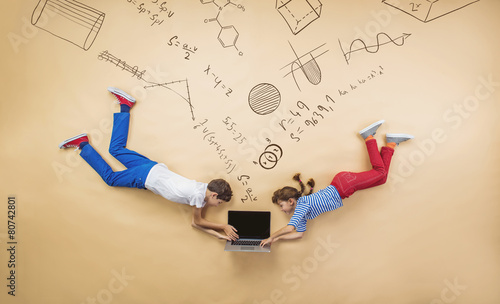 Cute boy and girl learning playfully in frot of a big blackboard - 80742801