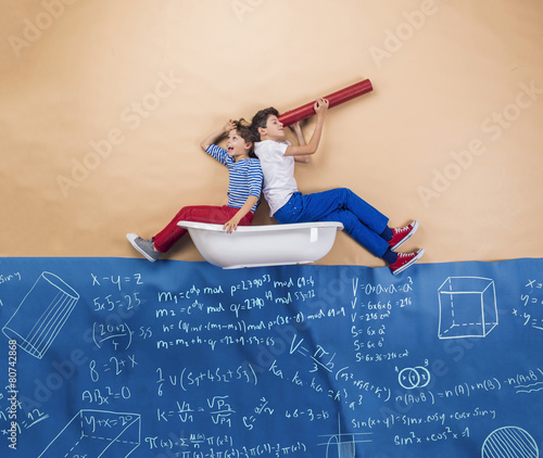 Cute boy and girl learning playfully in frot of a big blackboard - 80742868