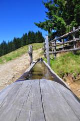 Holzbrunnen auf Wanderweg in den Alpen