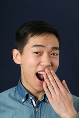 Young Asian man covering his opened mouth with his palm
