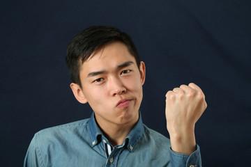 Funny young Asian man shaking his fist and looking at camera