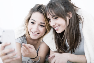 Two young roommates chatting with phone on the bedroom.