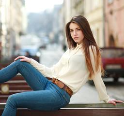 Fashion portrait stylish urban girl posing in old city street