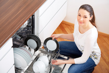 20s woman in kitchen, empty out the dishwasher 8