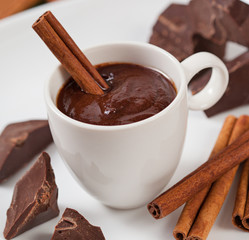 Hot chocolate in a cup, pieces of chocolate and cinnamon
