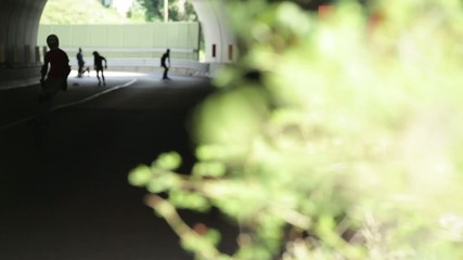 Downhill skateboarder in action on a asphalt road in a tunnel