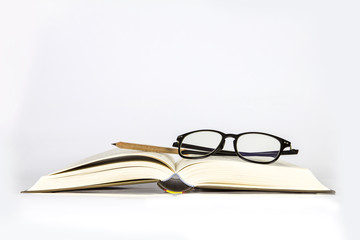 black rimmed glasses placed on opened book