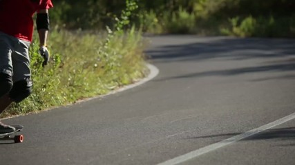 Downhill skateboarder in action on a asphalt road