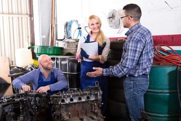 Mechanics repair engines at workshop