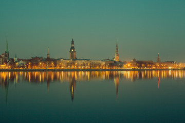 Night view of Riga with reflection in river, with retro colors