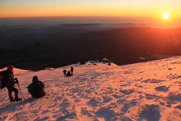 climbers on the slope of mountain at sunrise