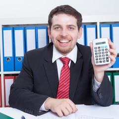Lachender Mann im Büro mit Taschenrechner