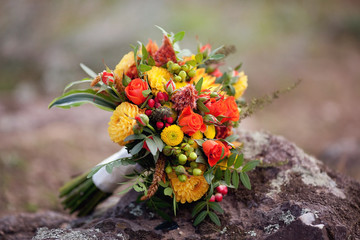 Orange wedding bouquet on the stone