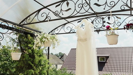 Close-up of a white wedding dress hanging under the roof