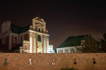 Baroque church by medieval wall at night in Poznan.