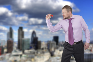 Businessman aiming by dart with modern city in background