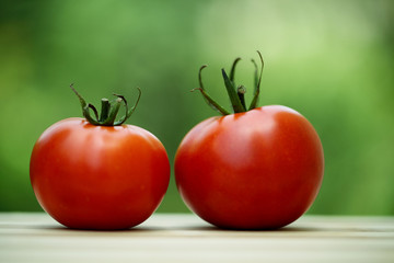 Red ripe tomatoes against green