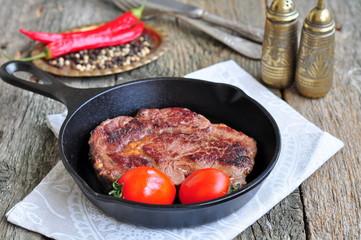 Juicy beef steak in a frying pan