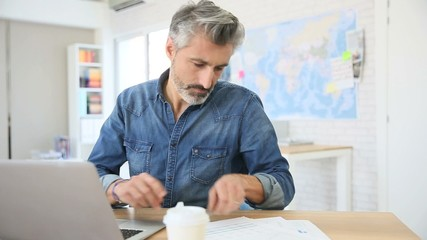 Mature man working on laptop in school office