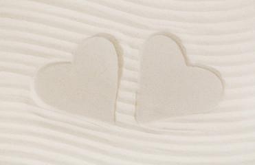 Zwei Herzen im Sand als Hintergrund für eine Grußkarte