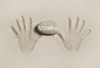 Achtsam leben im Alltag: Hände halten Stein mit Wort Achtsamkeit