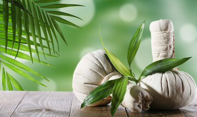 Spa compress balls with green leaves on green background