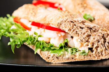 Prawn sandwich on black plate closeup