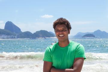 Lachender Latino im grünen Shirt an der Copacabana