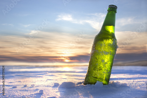 Plexiglas Bier bottle of cold beer at sunset
