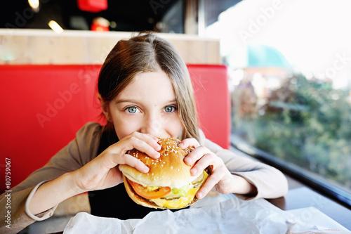 Cute little  girl eating a hamburger - 80759067