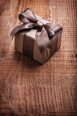 vintage paper gift box with brown bow on old wooden board