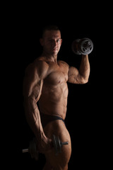 Sexy bodybuilder lifting weights and posing.