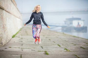 Woman exercising outdoors with a jump rope