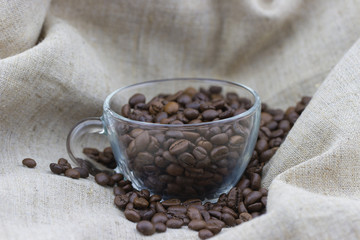 Roasted coffee beans in cup on sackcloth