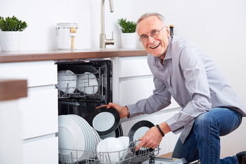 Senior man in kitchen, empty out the dishwasher 4