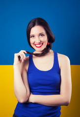beautiful young woman posing against blue and yellow background