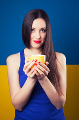 beautiful young woman posing with yellow cup against blue and ye
