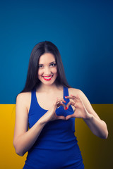 beautiful young woman making gesture of heart against blue and y