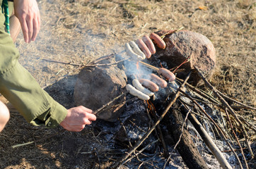 Cooking Sausages on Sticks over Campfire