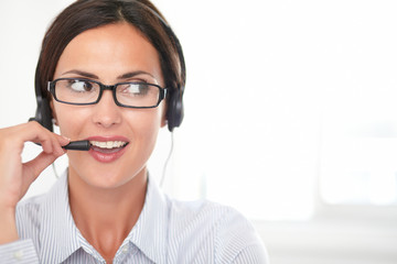 Confident young secretary talking on headphones