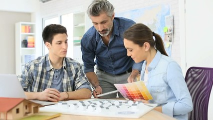 Teacher with students in architecture school