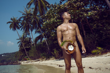 Sexy man on the deach with coconut.