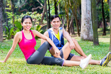 Couple doing sit-up in tropical Asian park