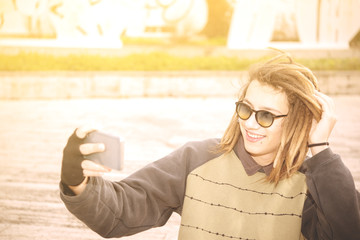 young handsome rasta teen guy with sunglasses selfie in the city